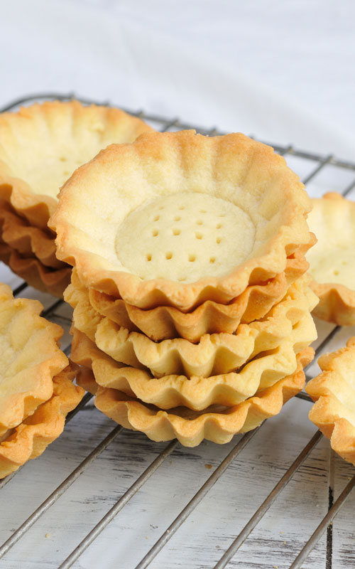 baked mini tart shells with on a cooling rack
