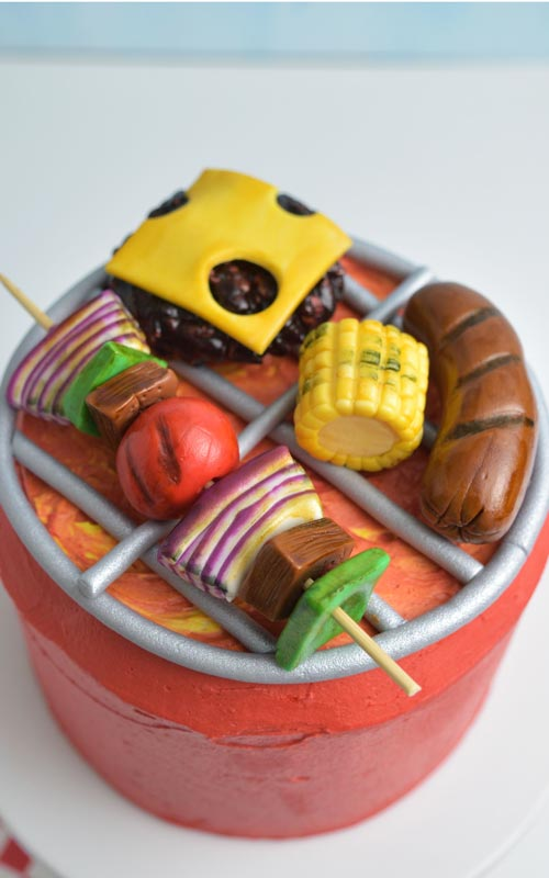 Red buttercream barbecue grill cake with fondant sausage, corn, kebabs, burger with cheese.