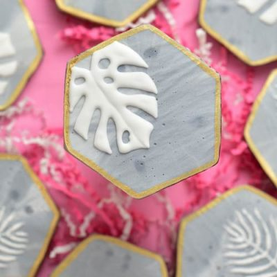 Cookie with concrete royal icing texture and monstera leaf plant designs.