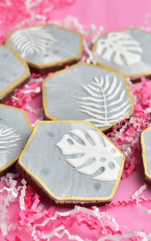 hexagon cookies with concrete texture royal icing and white monstera deliciosa leaves