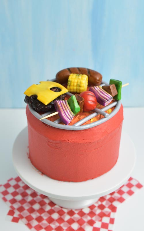 Red buttercream barbecue grill cake with fondant kebabs, corn, sausage and burger.