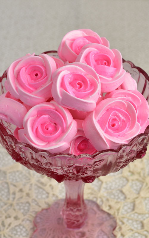 Pink meringue rose cookies in a pink glass bowl.