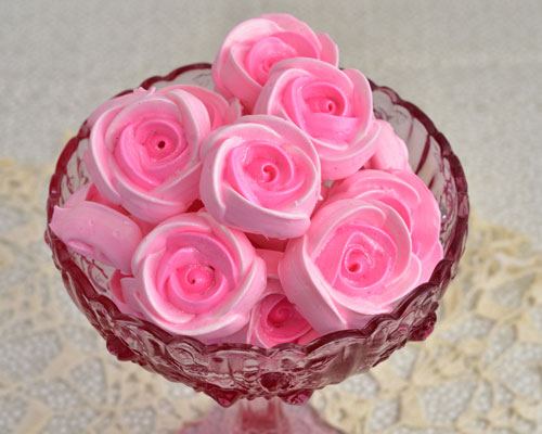 Pink meringue roses in a pink glass bowl.