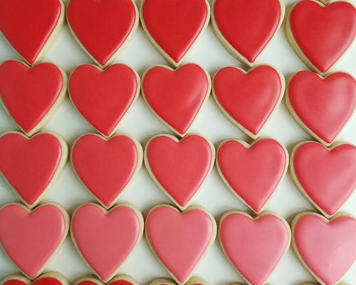 Red heart cookies iced with red 15 second royal icing consistency.