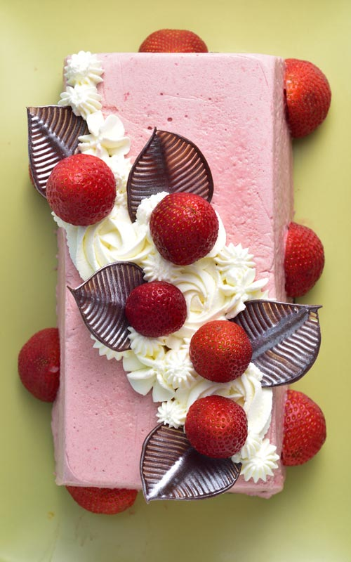 Pink strawberry mousse icebox cake decorated with chocolate leaves, fresh strawberries and whipped cream swirls.