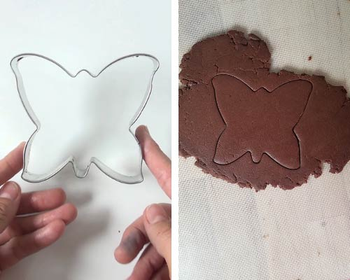 A hand holding a metal butterfly cookie cutter.