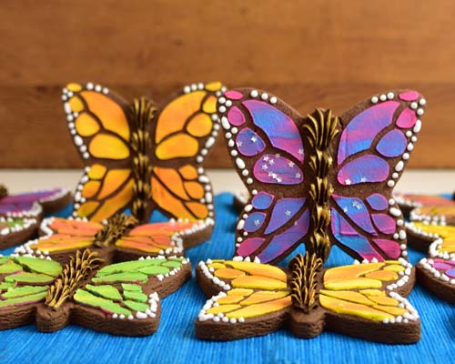 Butterfly cookies decorated with orange, yellow, pink and purple royal icing.