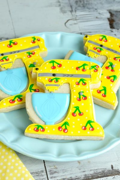 Yellow stand mixer cookies with cherry pattern on a blue plate.