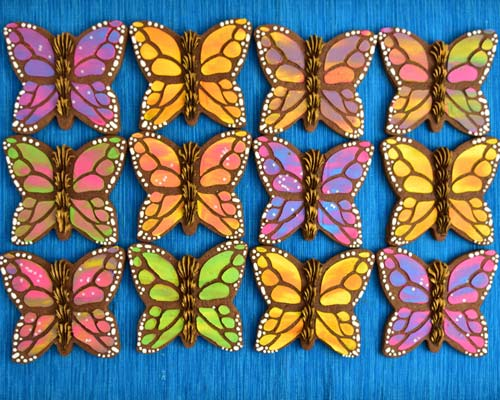 Colorful Butterfly cookies on blue tablecloth.