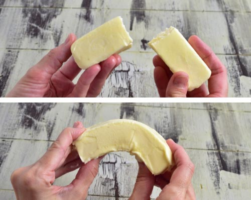 Holding butter with 2 hand bending it to see if it is at room temperature.