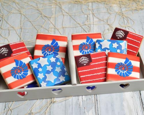 Seashell patriotic sugar cookies stenciled with royal icing.