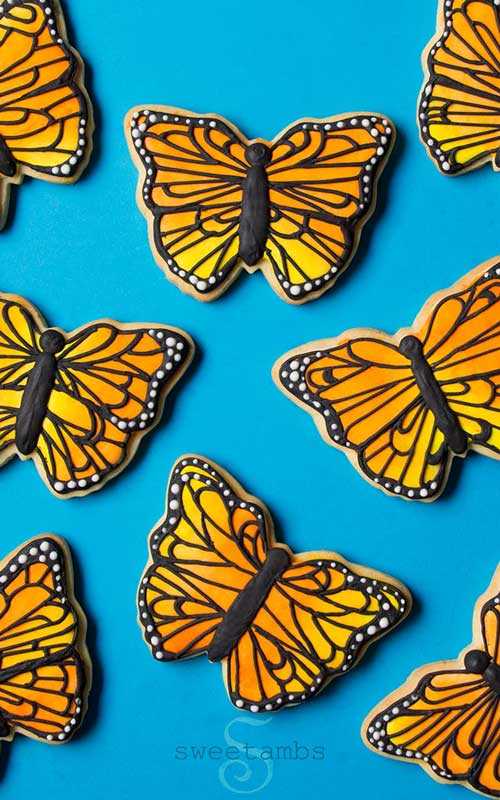 Yellow decorated monarch butterfly cookies on a blue background.