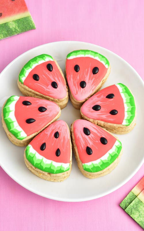 Watermelon pinata cookie arranged in a circle on a plate.