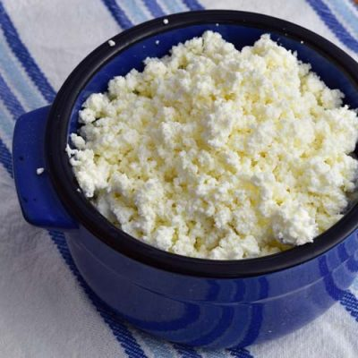 Crumbled homemade farmers cheese in a bowl