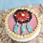 Raspberry mousse tart decorated with fruit and cookies
