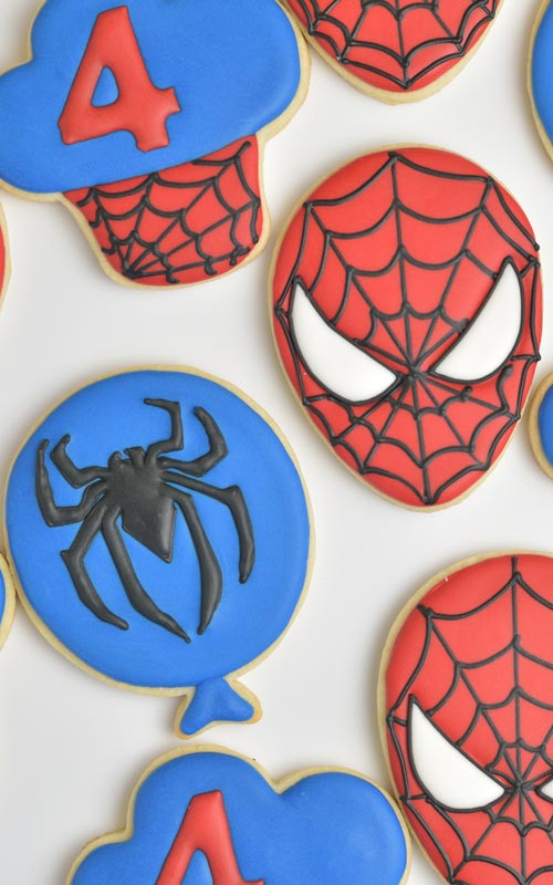 Cookie iced with red icing and decorated with black spiderweb design.