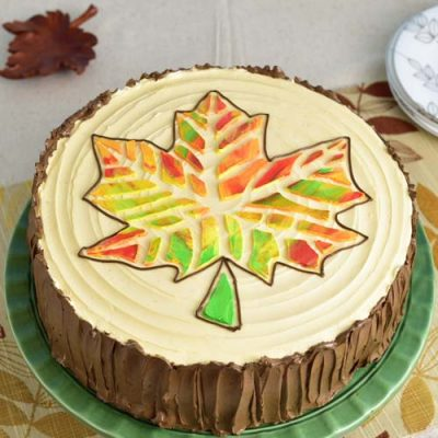 Colorful stenciled leaf cake on a green cake stand.
