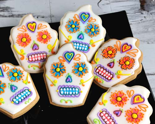 Decorated day of the dead cupcake cookie displayed on a black plate.