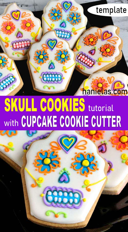 Royal icing decorated cupcake skull cookies on a black plate.