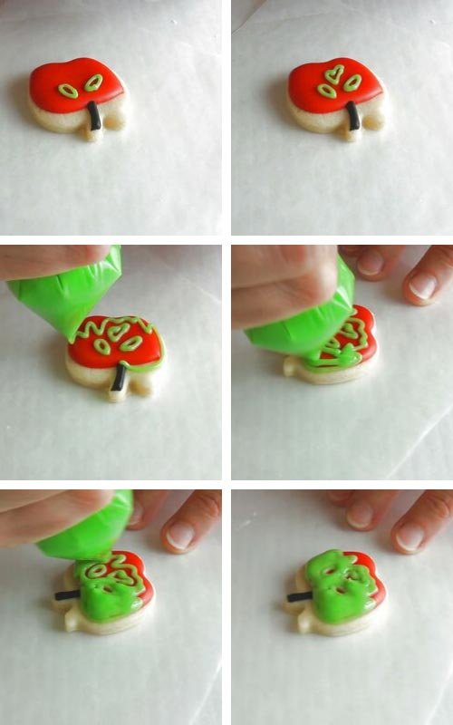 Decorating red apple cookie with green royal icing.