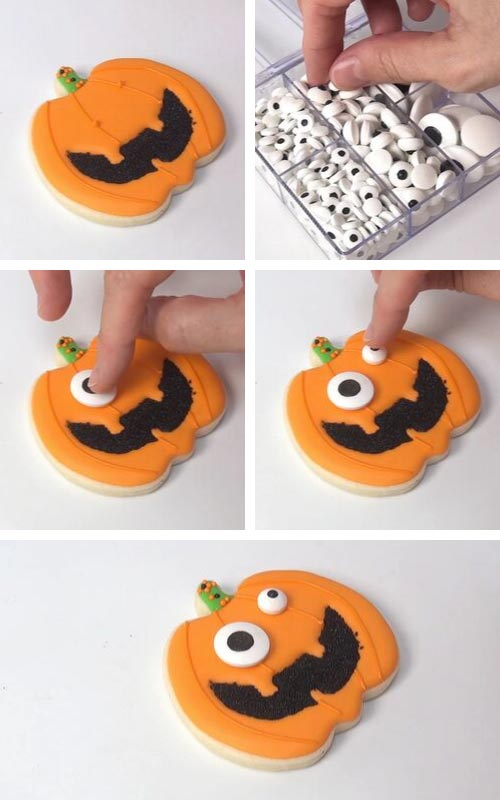 Attaching candy eyes onto jack o lantern cookies.