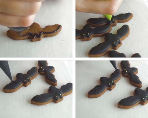 Decorating bat cookies with black royal icing.