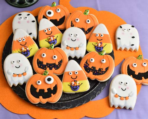 Jack o Lantern, Ghost and Candy Corn decorated cookies on displayed on a black plate.