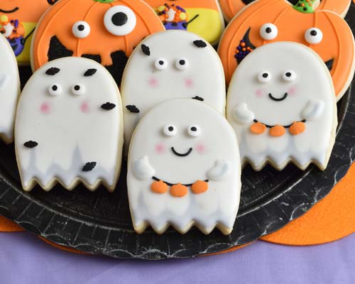 Decorated ghost cookies displayed on a black plate.