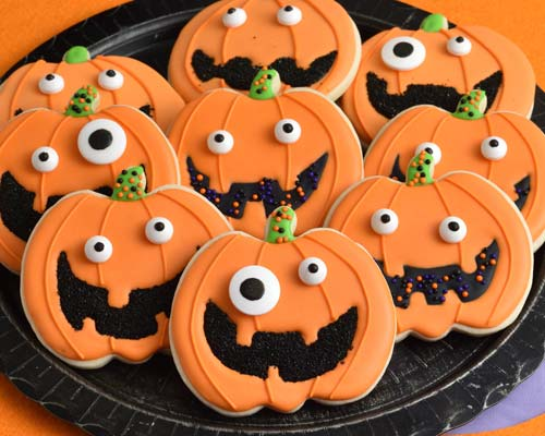 Decorated Jack o Lantern cookies on a black plate.