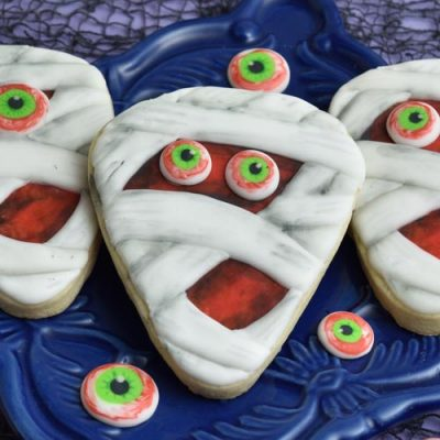Decorated mummy cookies on a blue plate surrounded with monster royal icing eyes.