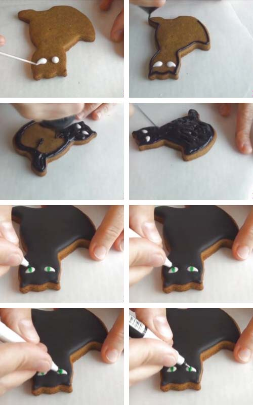 Decorating cat cookies with black royal icing.