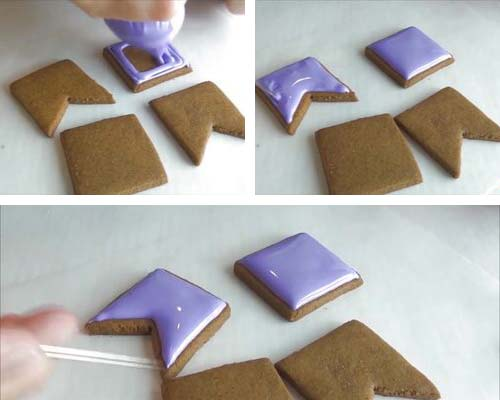 Icing chimney cookie panels with royal icing.