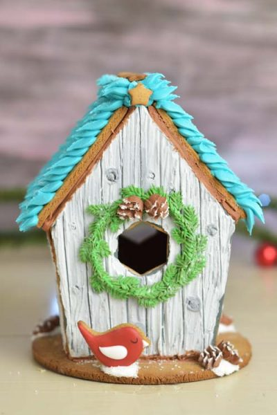 Gingerbread birdhouse displayed on a table.
