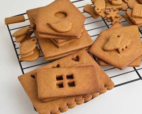Baked and cooled gingerbread house panels layered on a cooling rack.