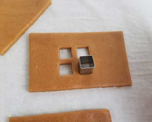Cutting out a small window from a cookie dough using a mini square cutter.