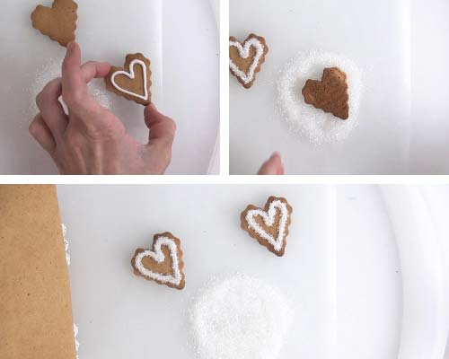 Piping white outline on a heart cookie and dipping it in white sanding sugar.