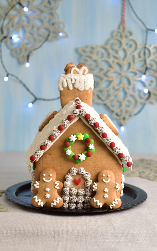 Candy decorated gingerbread house on a black plate.