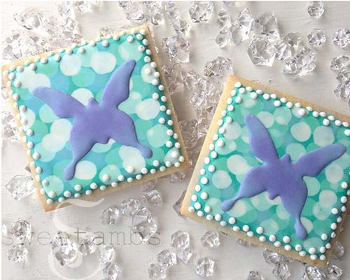 Decorated butterfly cookies on a white background surrounded by clear gems.