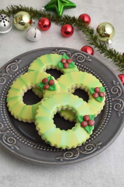 Royal icing decorated cookies shaped like wreaths displayed on a pretty gray plate.