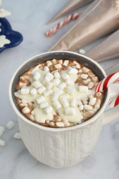 Mug filled with hot cocoa topped with chocolate snowflake and marshmallows.