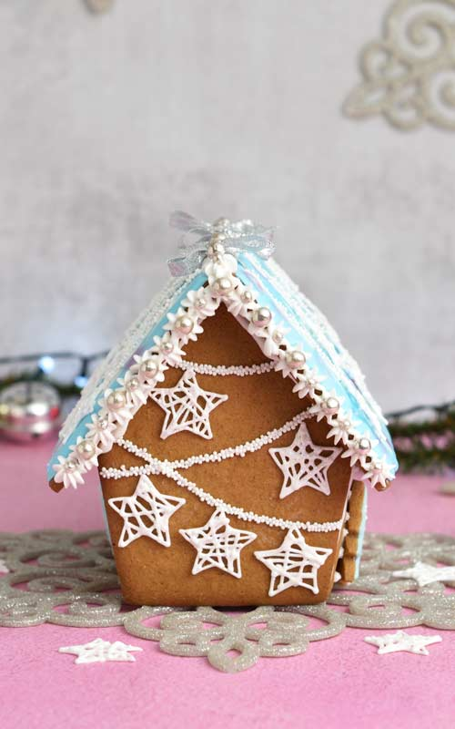 Back of the gingerbread house showing piped strings and handing royal icing star wire ornaments.