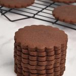 Baked scalloped edge cookies stacked on top of each other.