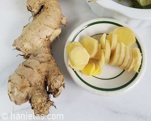 Peeled and sliced fresh ginger on a plate.