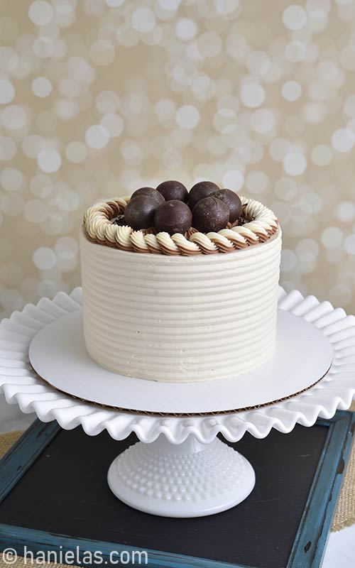 Buttercream cake with chocolate spheres on the top.