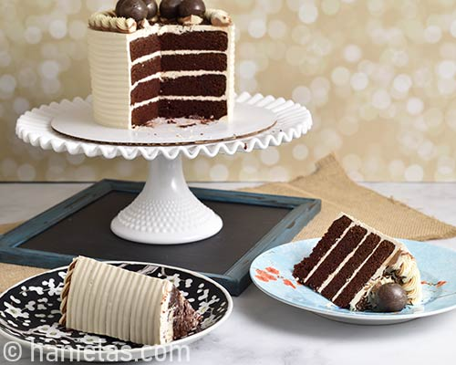 Cake on a cake stand and cake slices on plates on a table.