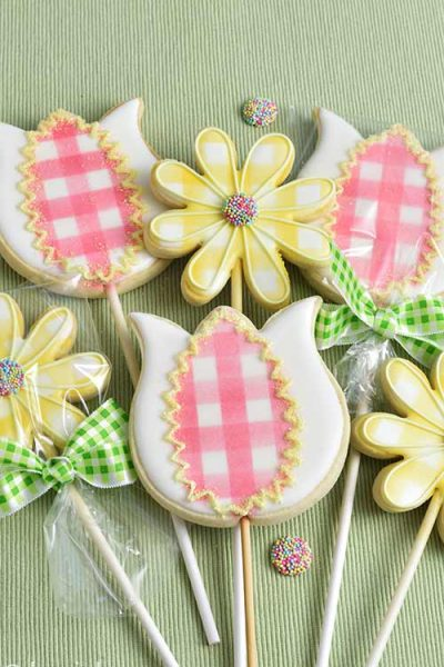 Decorated cookies on a stick arranged into a bouquet.