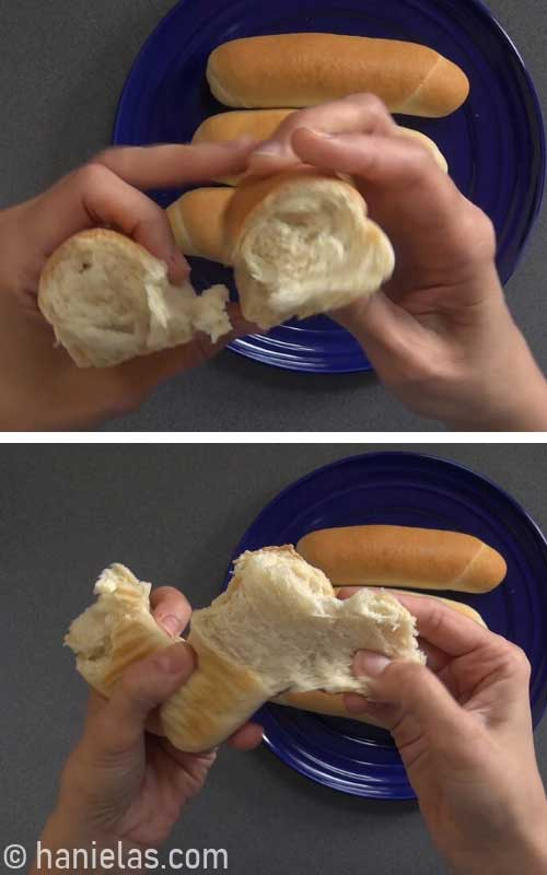 Tearing bread bun in half showing the texture and inside.