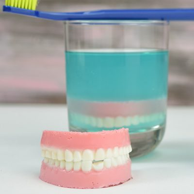 Jello denture in front of a drinking glass filled with jello.