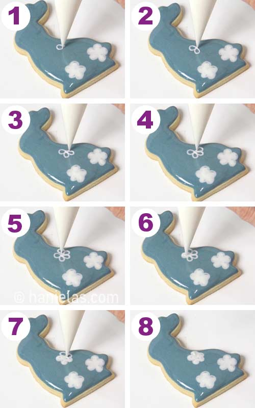 Piping wet on wet daisy flowers onto a freshly royal icing iced cookies.