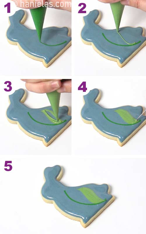 Piping a wet on wet royal icing leaf onto a freshly iced cookie.